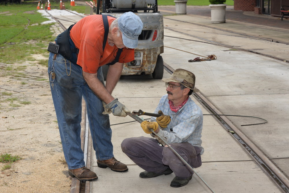 (L-R) BSM Member #241, Dennis Yeager and BSM Member #739, vice president, Operations, John La Costa prepare new Trolley Overhead Wire that will carry the 600 Volts Direct Current that powers the streetcars, August 2017. Image Credit: Jim Walsh