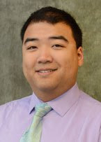 A headshot of Dr. Lee in front of a olive grey backdrop.