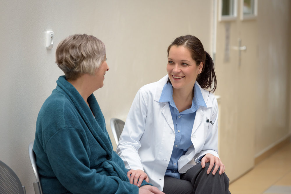 smiling-female-doctor-talking-to-senior-patient-in-hospital_BFBkxIpNs.jpg