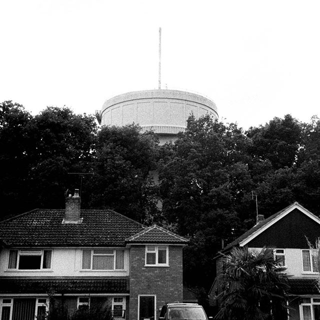 Water tower located in a residential area. Or a UFO?  #bw #blackandwhite #35mm #film #photography #konica #af3 #ilfordfp4 #nature #watertower #water #structure #architecture #juxtaposed #juxtapoz #ostentatious #neoclassical #wildernessculture #wilderness #moody #overcast #contrast #storm #exploring #filmgrain #noise #UFO #alien