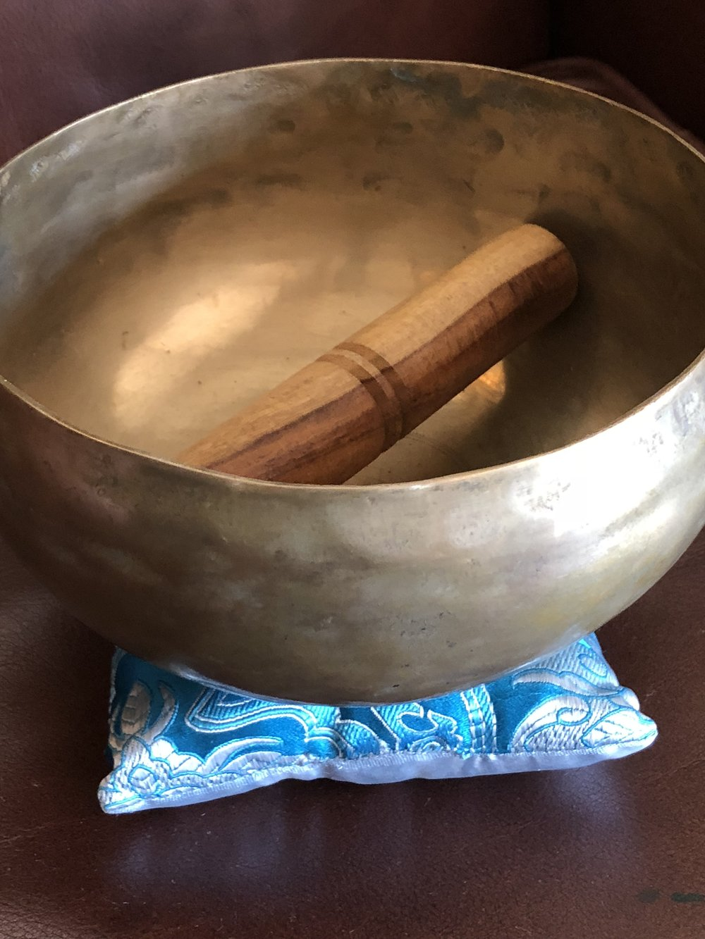 Brass singing bowl with blue pillow