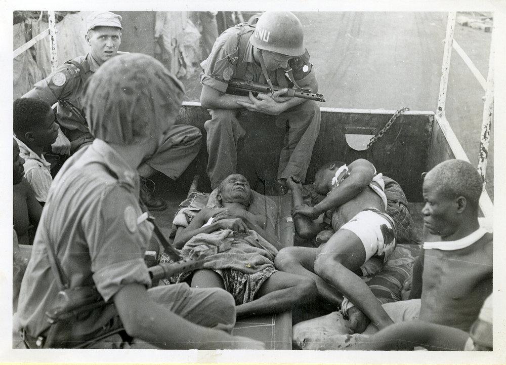 """""""Sårade balubas förs bort av oss till sjukan"""". Bataljon XII. Baluba är ett bantufolk i Centralafrika, främst i regionerna Kasaï och Katanga i Kongo-Kinshasa."""