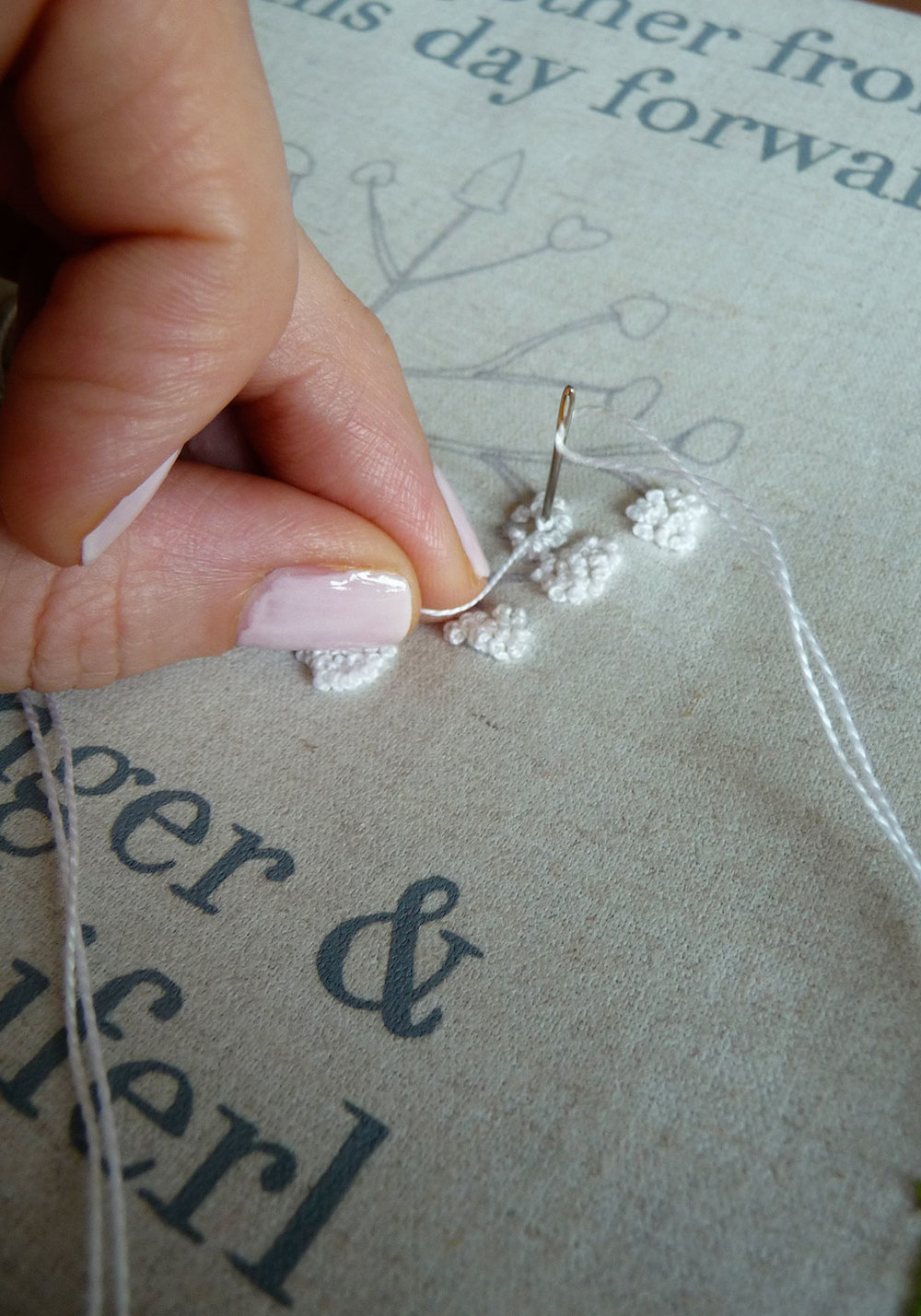 Embroidering the french knots using a white silk thread