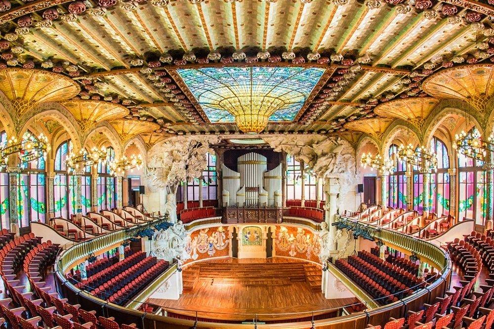 Palau de la Música Catalana, Barcelone - Le Palau de la Música Catalana est une salle de concerts inscrite au Patrimoine mondial de l'Humanité par l'UNESCO et construit au début du XXe siècle par l'architecte Domènech i Montanerpour être le siège de l'Orfeó Català. Cet édifice, du courant 'moderniste' est un joyau du patrimoine architectural et musical de Barcelone et conjugue sur sa magnifique façade la sculpture, la mosaïque, les vitraux et la forge.