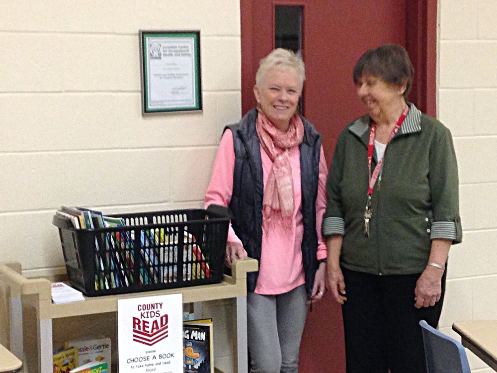 Barbara Wallace from County Kids Read and Sandra Brighton from the Salvation Army stand beside the basket of books at the food bank at the Salvation Army on Elizabeth Street in Picton.  Families and children visiting the food bank are encouraged to choose a free book to take home.