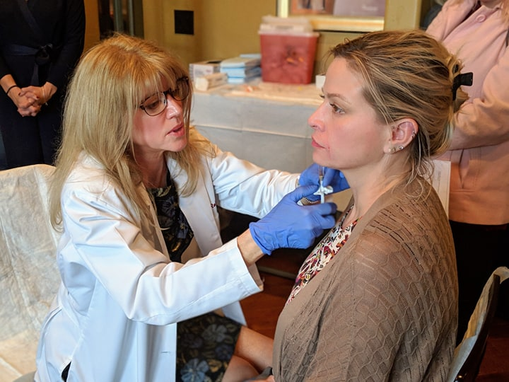 Dr. Roberts injecting a model at an aesthetic open house on December 8th, 2018.