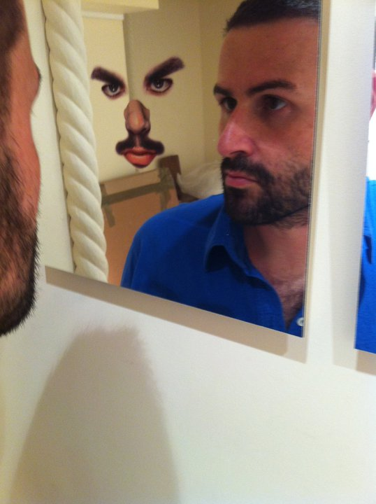 Arnaud faces his reflection in the stache mirror