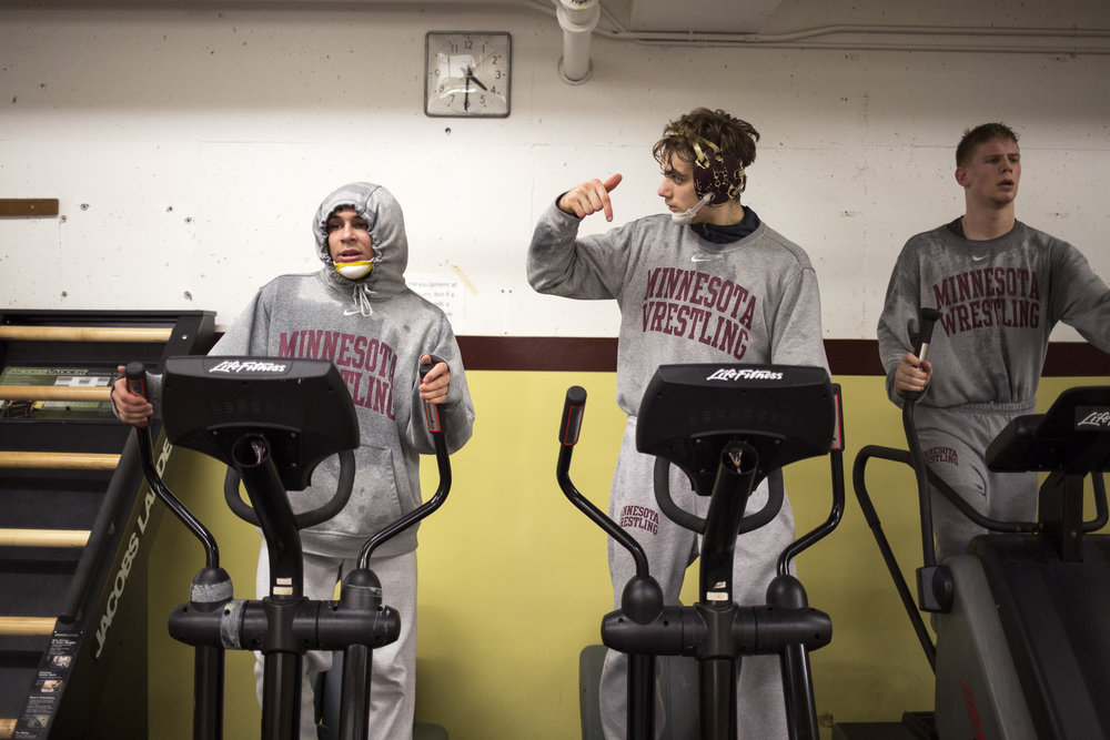 Sweating through their heavier athletic clothes, Fredy Stroker, left, Colin Carr and Chris Pfarr opt to execute conditioning exercises after practice. Weight management is second nature to most wrestlers, who know that an extra pound on the scale could mean disqualification from competing within their weight class.