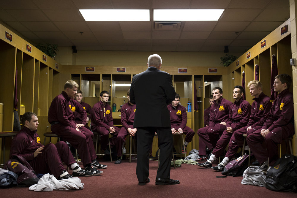 "Head coach J Robinson delivers a speech to the team before a home dual meet at the Sports Pavilion. Robinson, who has led the Gophers wrestling team for 30 seasons, described these moments before competition as a time when each athlete practices his own method of becoming focused. Robinson said the goal of his pre-competition speech is to ""have them believe in their training"" so that ""when they step on the mat, when they step into the arena, they are mentally tuned and ready to go."""