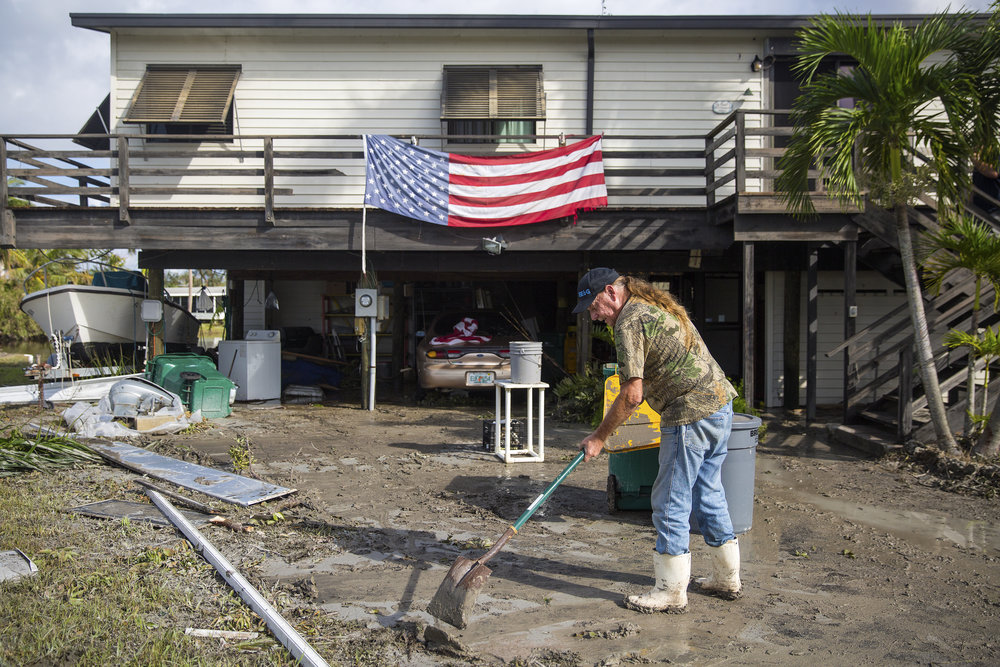 Harvey Pennell works to shovel a thick layer of mud from the driveway of his home in Plantation Island, an unincorporated area nearby Everglades City, as Collier County began picking up the pieces in the aftermath of Hurricane Irma on Tuesday, September 12, 2017.