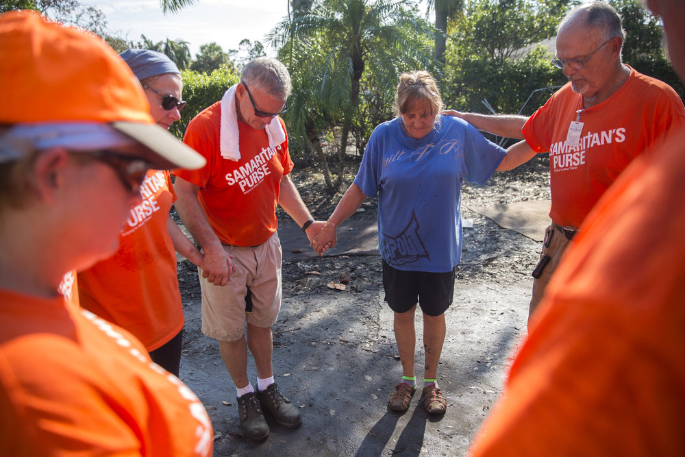 Lori Malone is joined in prayer by volunteers from Samaritan's Purse humanitarian aid outside of her damaged home in Bonita Springs on Tuesday September 26, 2017. Malone was finally able to begin clearing out the interior of her house this week, which is now riddled with mold, after several feet of standing water from Hurricane Irma flooded the neighborhood.