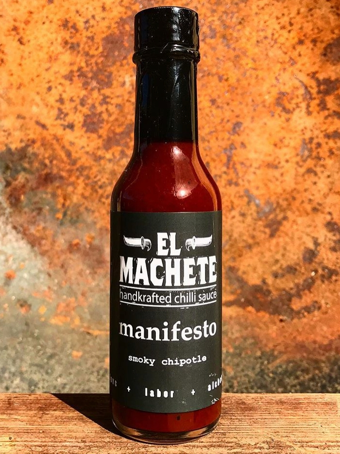 Manifesto - Manifesto is the first sauce created by the El Machete brand. This light, semi-sweet BBQ sauce character offers a savory, smoky, and tangy heat achieved by combining smoked Morita chillies, fire roasted Orange Habaneros, and toasted arbol chillies.It's further layered with a blend of Mexican style spices, organic Agave nectar, white and apple cider vinegar, and Kosher/natural sea salt. Manifesto adds smokiness to dressings, steak sauces, roasted chicken, cheese sandwiches, pizza, cheeseburgers, and can heat up smoky Mezcal cocktails.Heat level: 5 / 10.