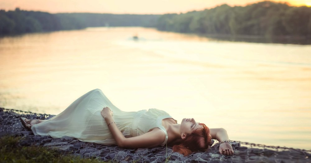 Woman lying by river