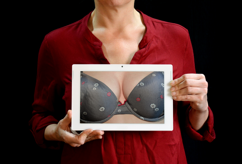 woman holding tablet with bra visible
