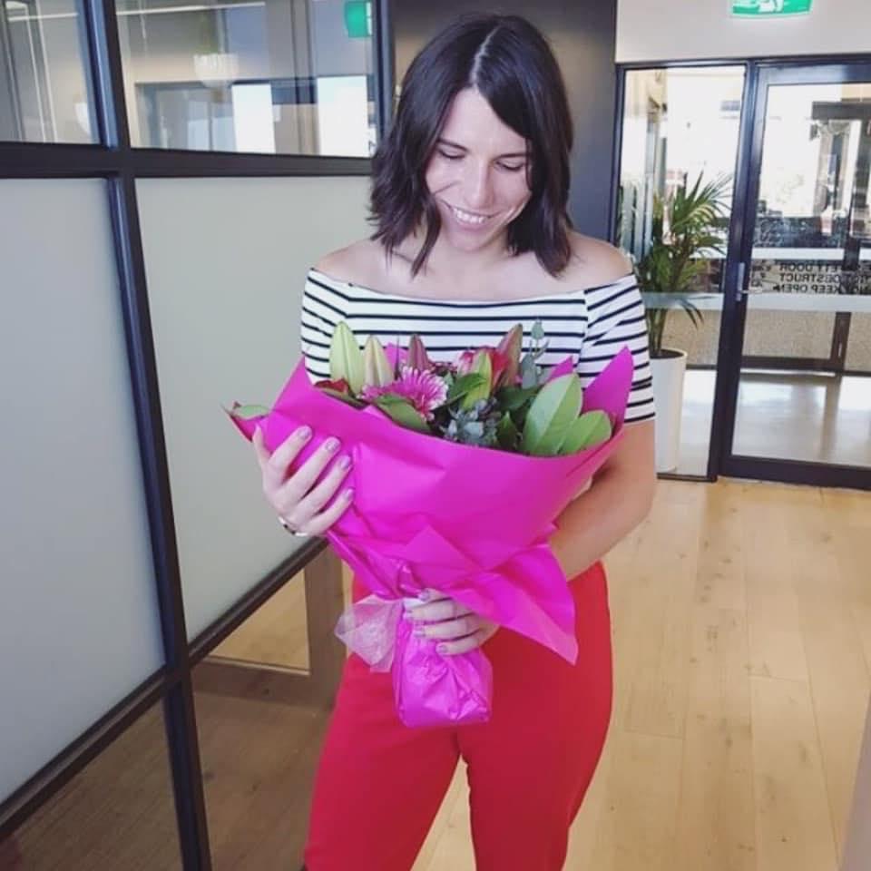 Cass holding a flower bouquet on her birthday, 2019