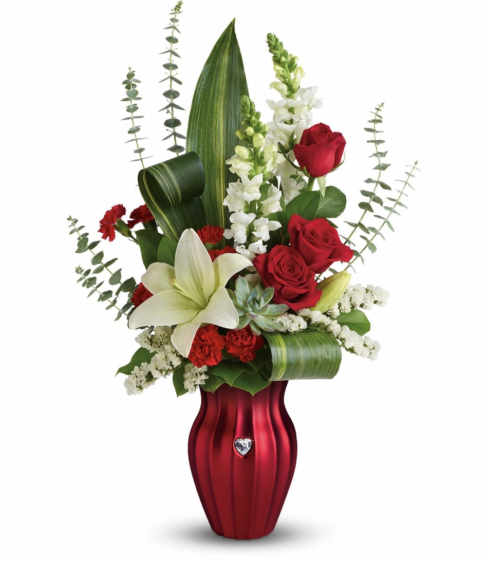 Splendid lilies, roses, snapdragons are accented by tropical greens and eucalyptus to give that WOW factor! -