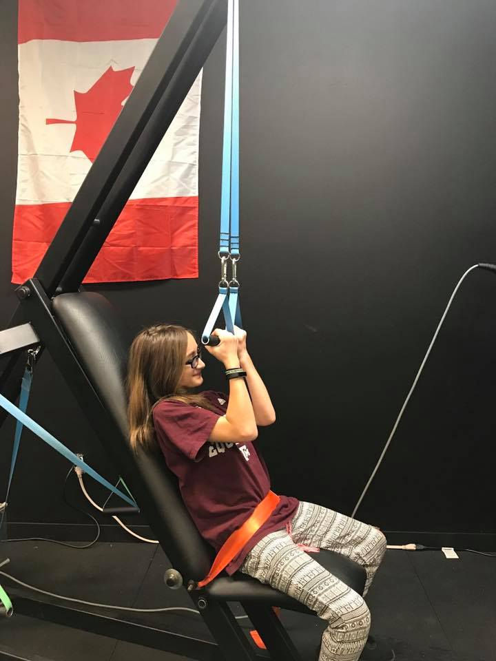 Girl pulling down on innovative health and performance outstrip exercise bands