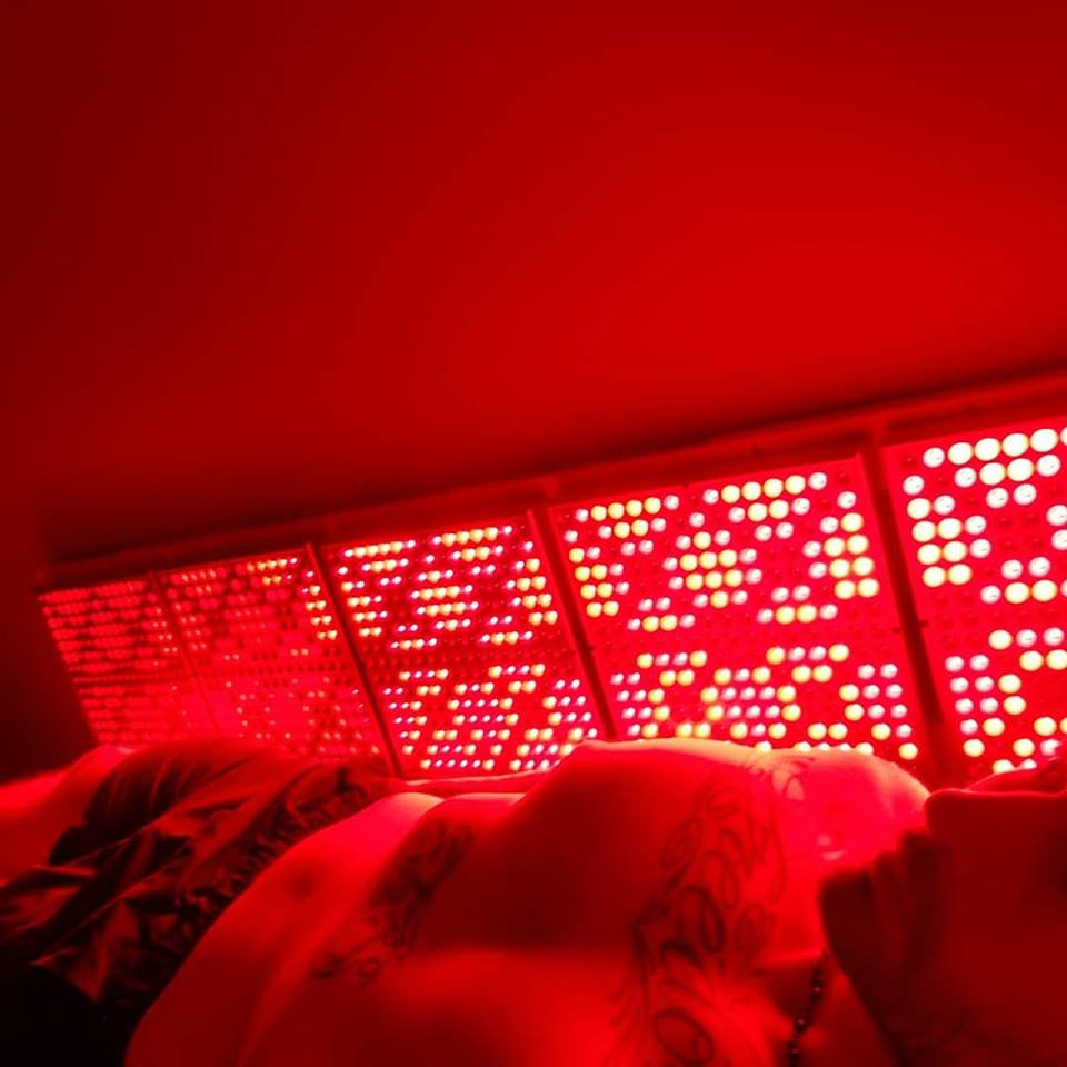 Person inside Innovative Health and Performance REDjuvenator red light therapy box
