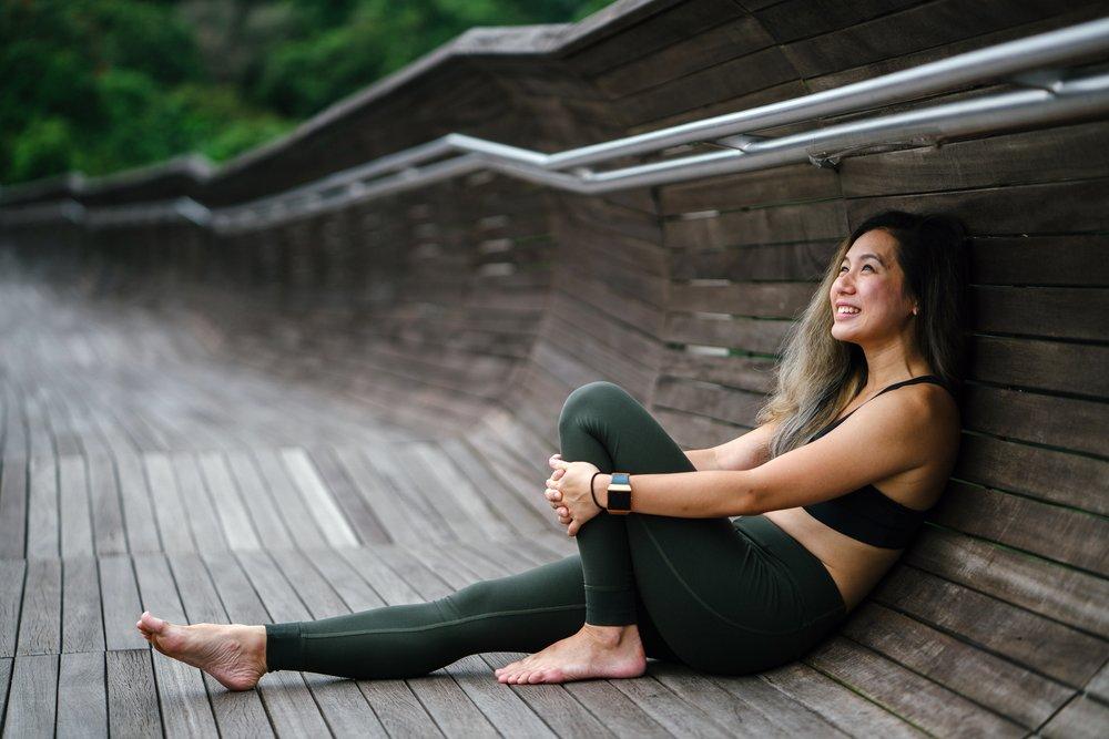 Girl in workout leggings on outdoor bridge smiling
