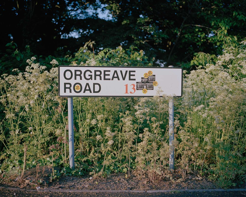 Road sign adorned with Orgreave Truth and Justice Campaign stickers, Orgreave, South Yorkshire.