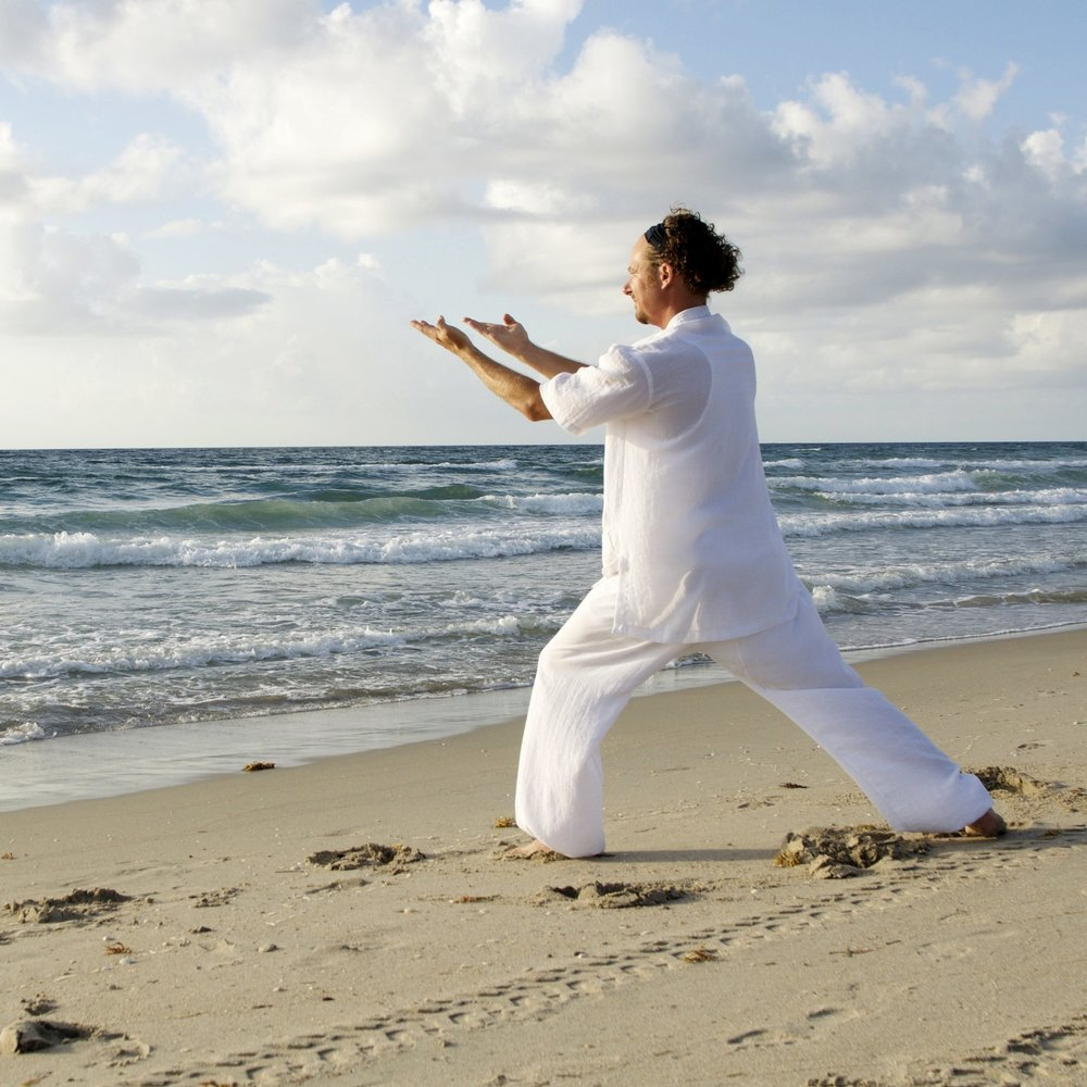 man-dressed-in-white-praticing-tai-chi-on-beasch.jpg