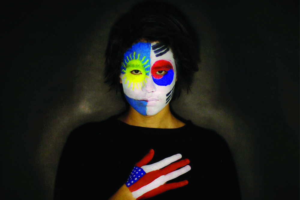 My name is Valeria Flores and I've created this photo for the Tolerance Education Center. This photo represents identity in oneself, I took a photo of my brother who represents a first-generation American who is biracial. As you can see in the photo his face is painted with the Argentinian flag and the South Korean flag which by blood that is his ethnicity. You then can see on his right hand it is painted with the American flag which is placed over his heart to represent that by heart he stands as an American regardless of where his parents came from. His face painted with the flags representing his parent's country of origin shows who he is but no matter what will always feel the proud acceptance of being born and raised as an American. Photo by: Valeria Flores