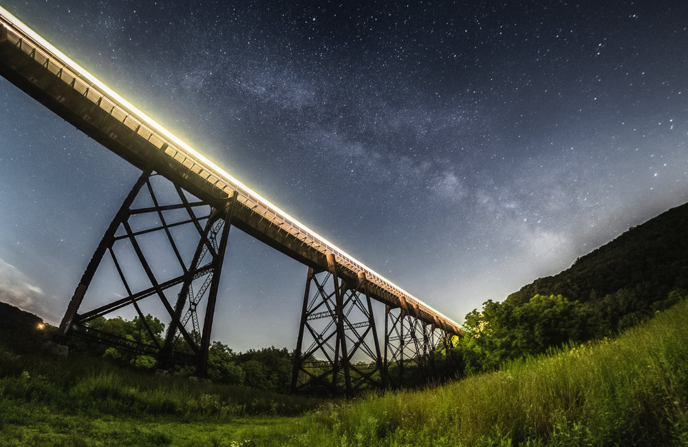 The Moodna Viaduct with train light trail and the Milky Way behind.