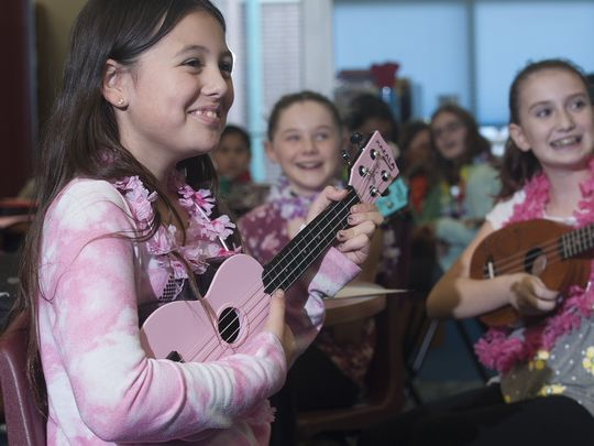 Evesham's J. Harold Van Zant Elementary School student, Isabella Moscharis, left smiles as she plays music during ukulele club. The school started the 4th & 5th grade club with a $500 personal donation that bought 15 little string instruments. Months later, she won a contest, acquiring 60 more ukuleles.  (Photo: Jose F. Moreno/Staff Photographer)