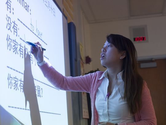 Quynh Nguyen writes Mandarin characters on a smart board during Mandarin Chinese class at Brimm Medical Arts High School in Camden. (Photo: Jose F. Moreno/Staff Photographer)