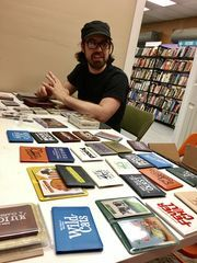Jason Tagmire, owner of card game company Button Shy, sits among his company's wallet games in a small office in Tiki Tiki Board Games in Woodbury. (Photo: Carly Q. Romalino/Staff photographer)