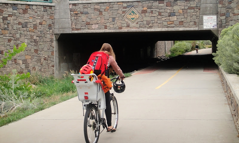 A mama cycling with her toddler on a bike path in Boulder, Colorado.