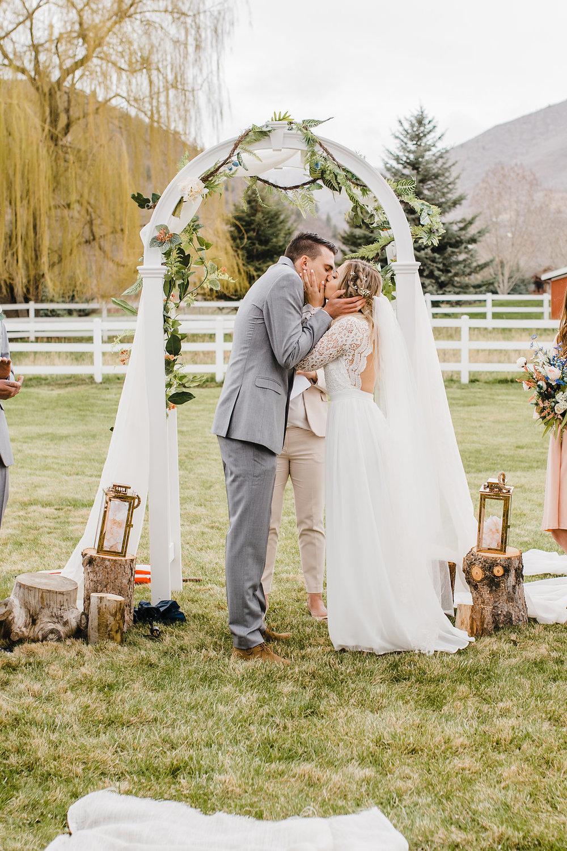 wedding ceremony park city utah florals arch lace dress kissing photo