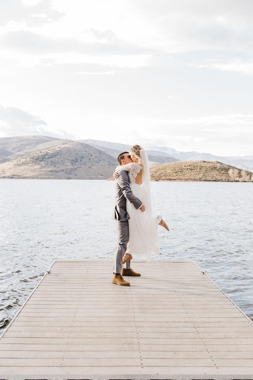 bride and groom kiss on a dock lake photos wedding photography park city northern utah