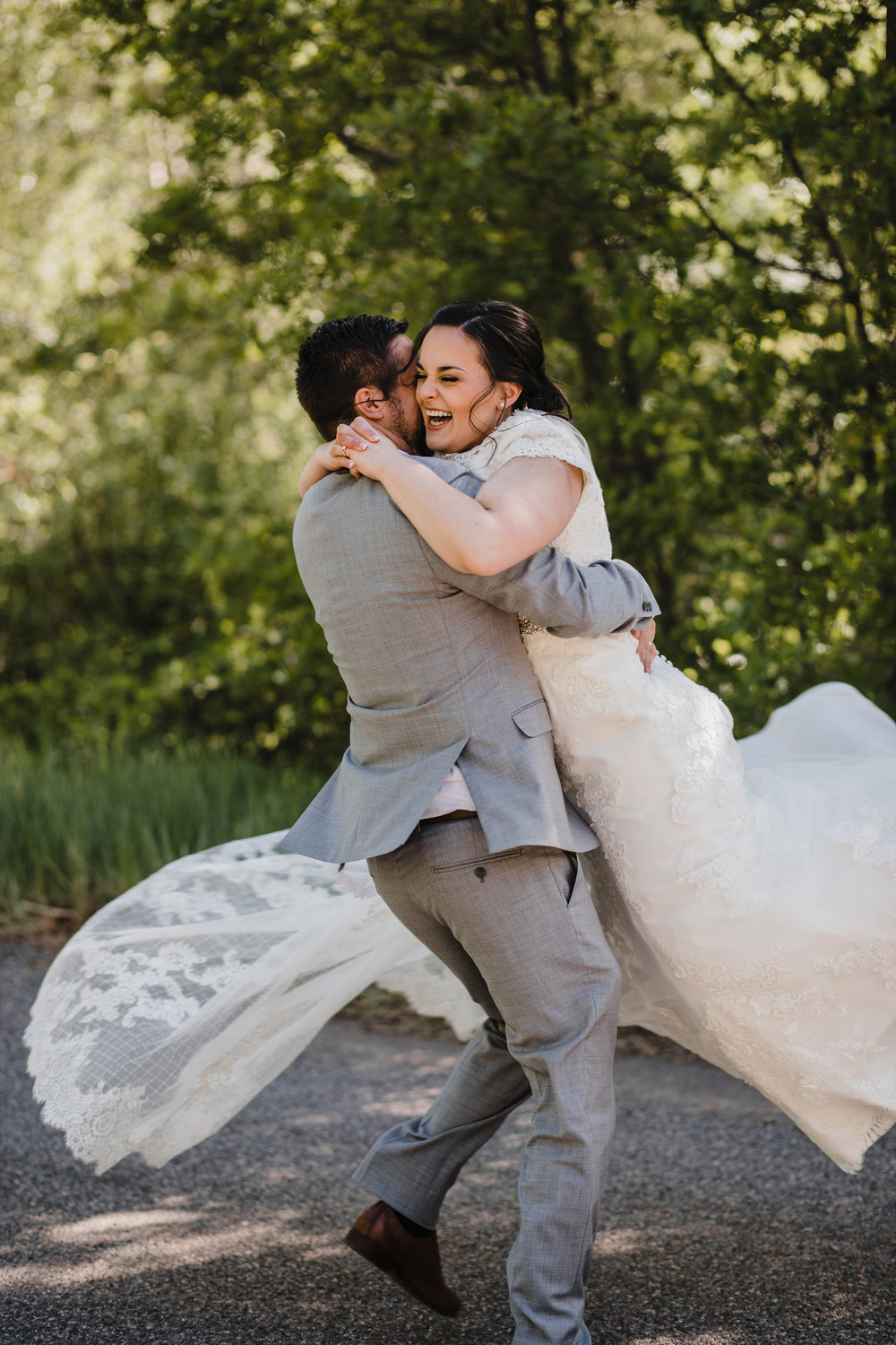 professional photographer in westminister colorado spinning laughter happy bride gray suits