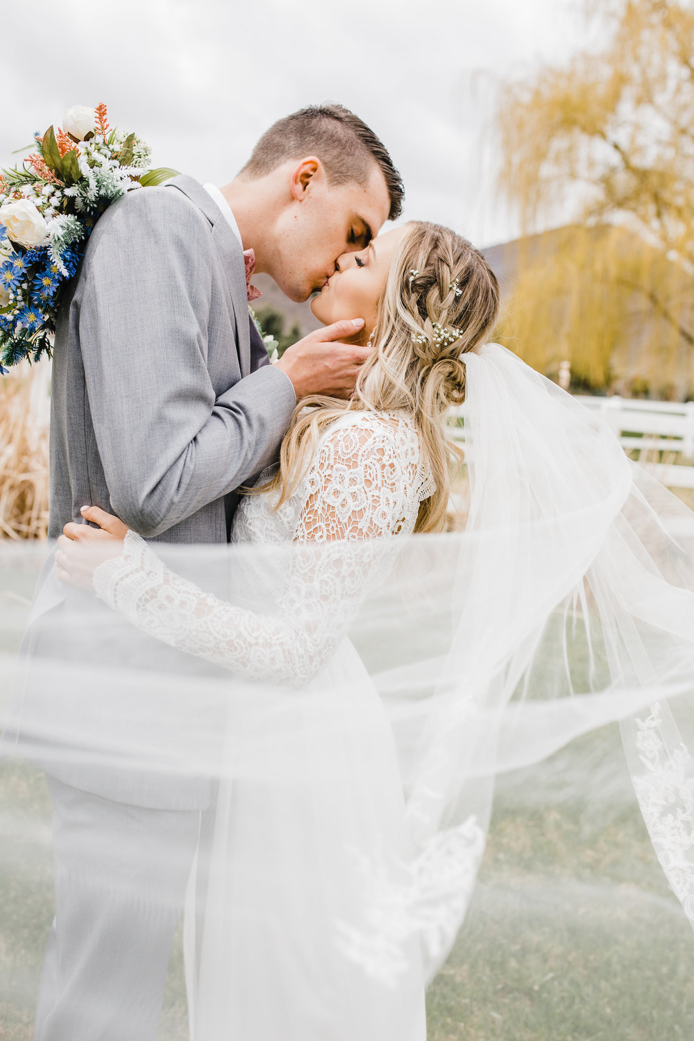 best wedding photographer in park city utah kissing romantic spring wedding wedding veil wedding hair