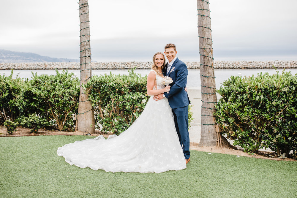 professional wedding photographer in park city utah wedding dress train bride and groom palm tree beach wedding smiling