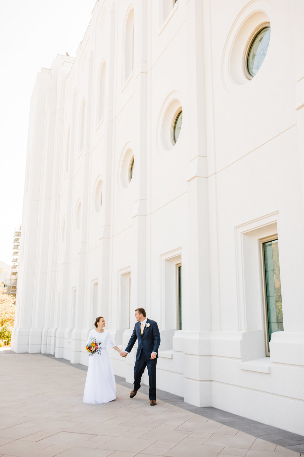 logan utah wedding photographer lds temple wedding holding hands bride and groom