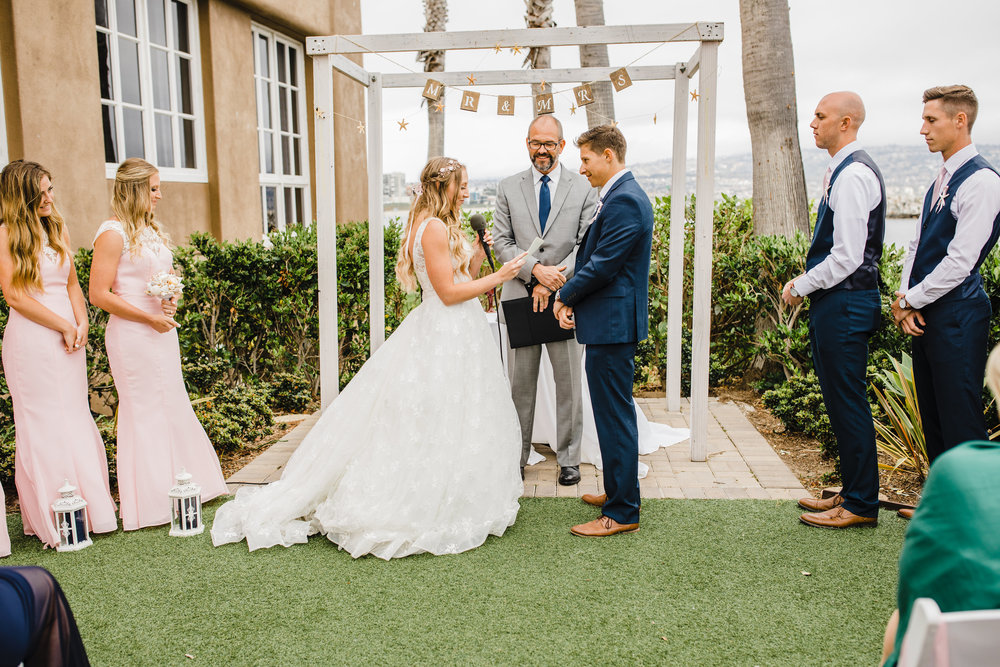Professional wedding photographer in lakewood colorado outdoor wedding ceremony vows wedding arch pink bridesmaids dresses