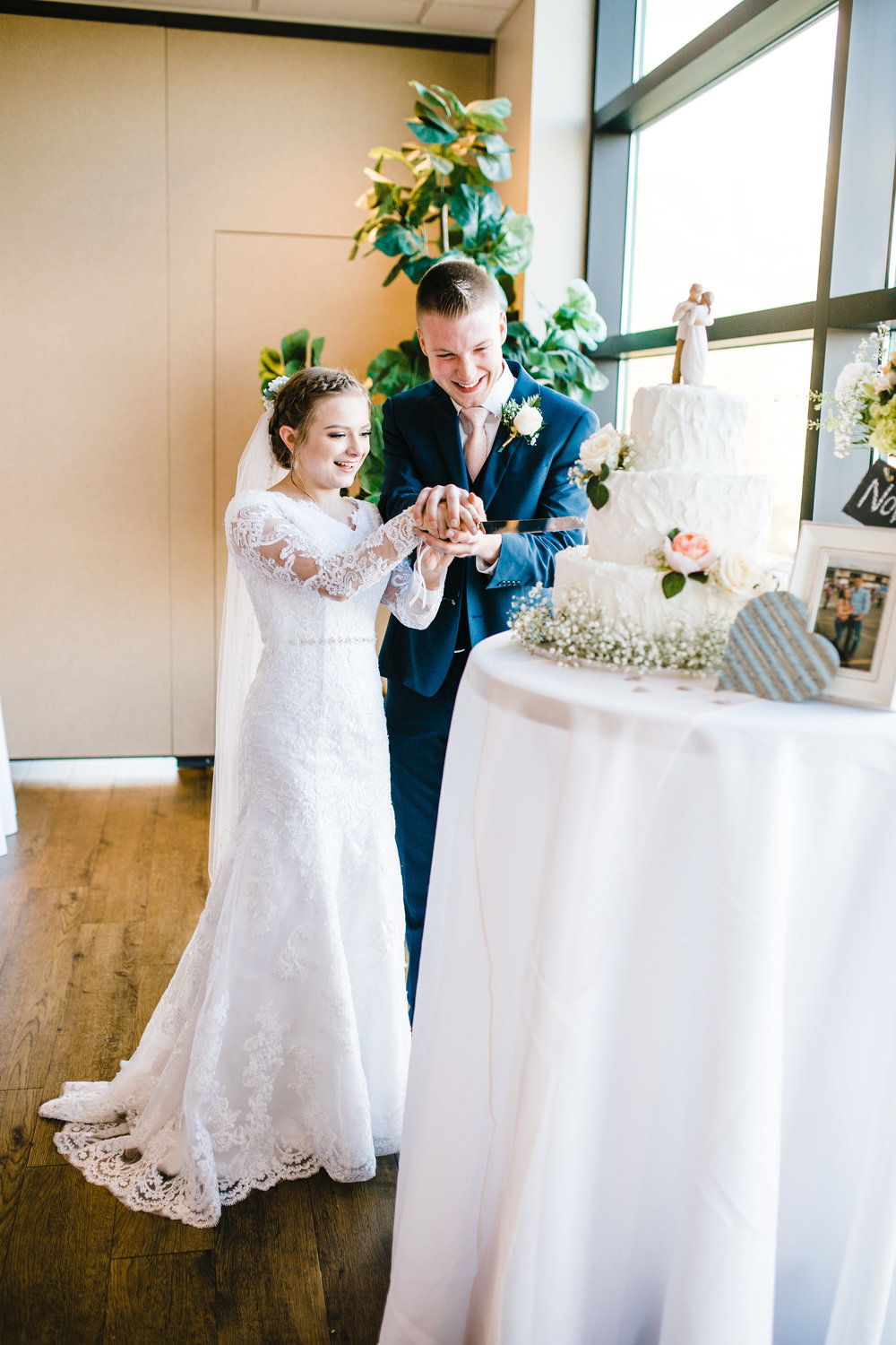 professional reception photographer wedding day arvada colorado bride and groom cutting the cake natural light