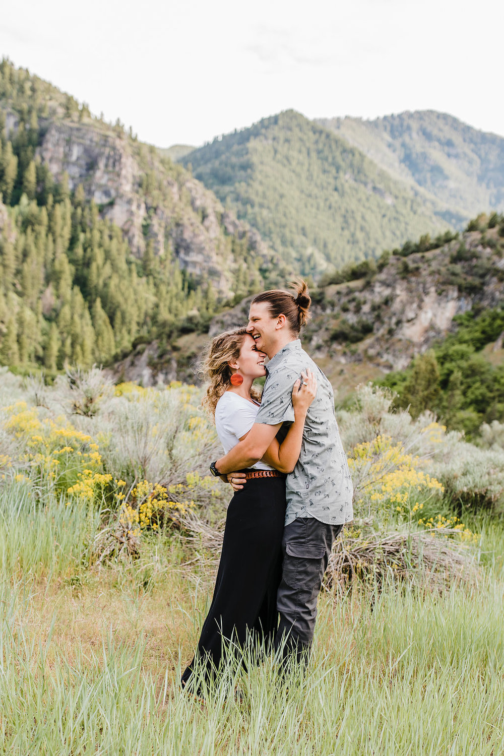 utah wildflower engagement photo couple hugging and laughing professional northern utah wedding photographer calli richards