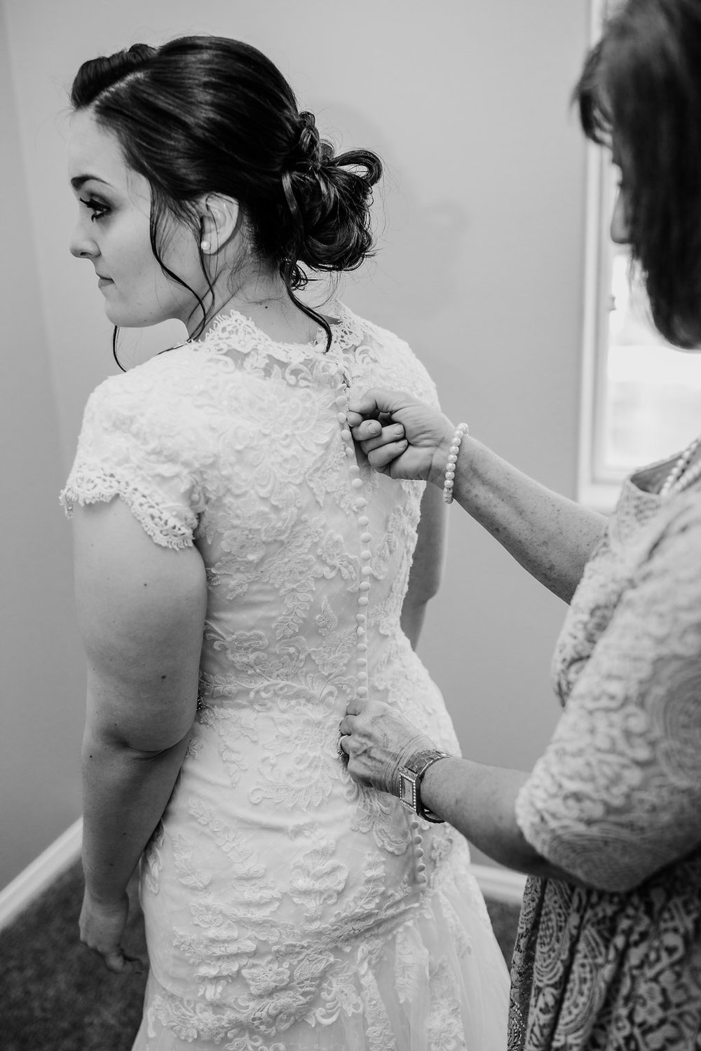 bride wedding day prep button down wedding dress black and white wedding photography utah