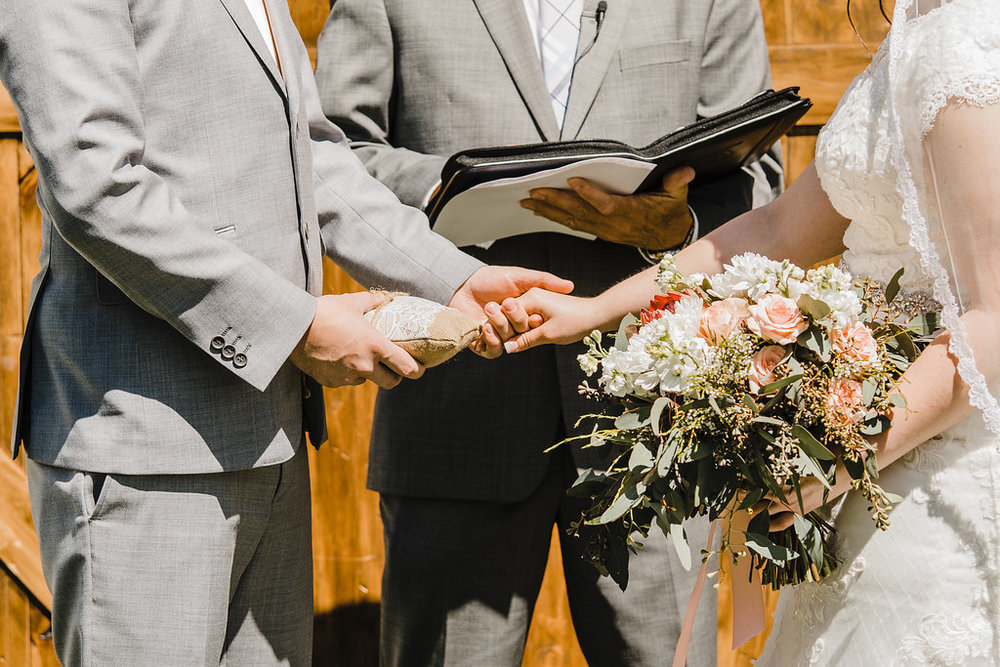 wedding ceremony bride and groom holding hands grey suits rose bouquet