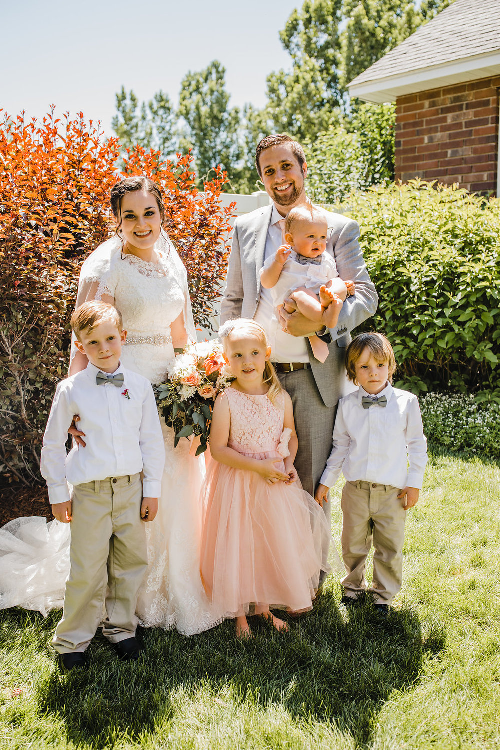 family photos on wedding day bride and groom with flower girl and ring bearer bowties utah wedding photography