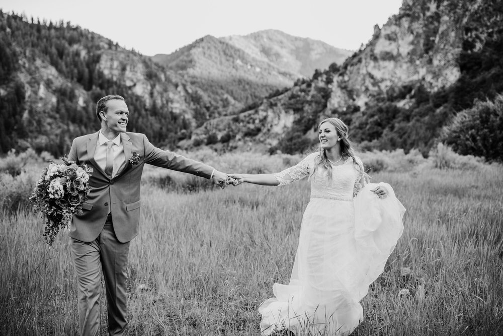 professional wedding photographer in Cache Valley holding hands laughing running mountain wedding