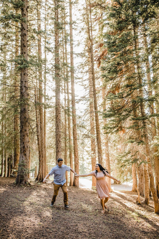 logan utah engagement photographer tall trees running holding hands laughing peaking sun