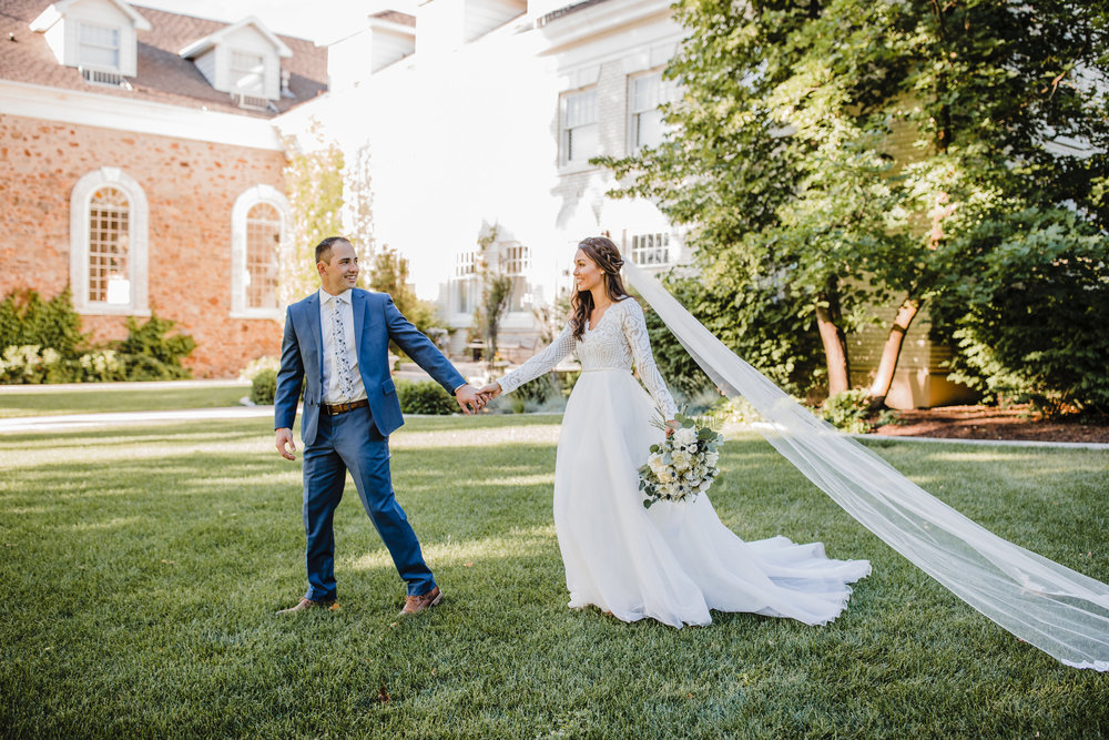wedding photographer in logan utah long veil holding hands smiling bride and groom