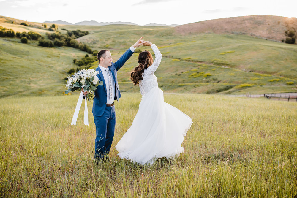 wedding photographer in logan utah spinning long veil field mountains