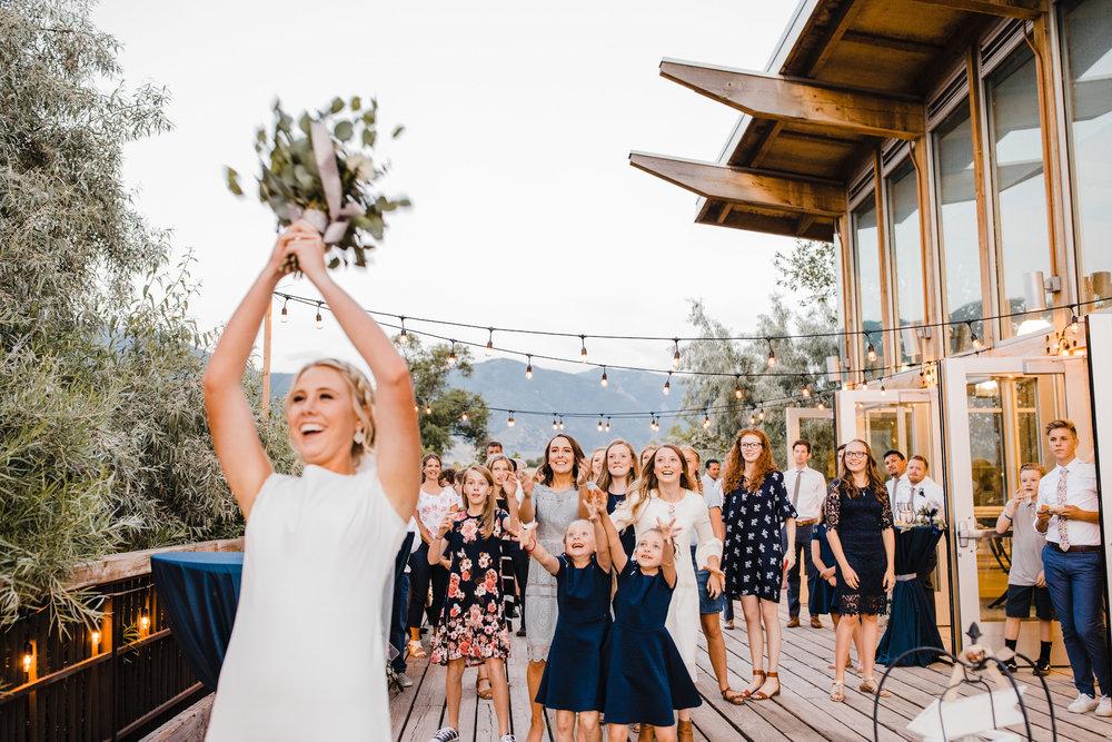 wedding photographer in utah valley wedding reception smiling bouquet toss