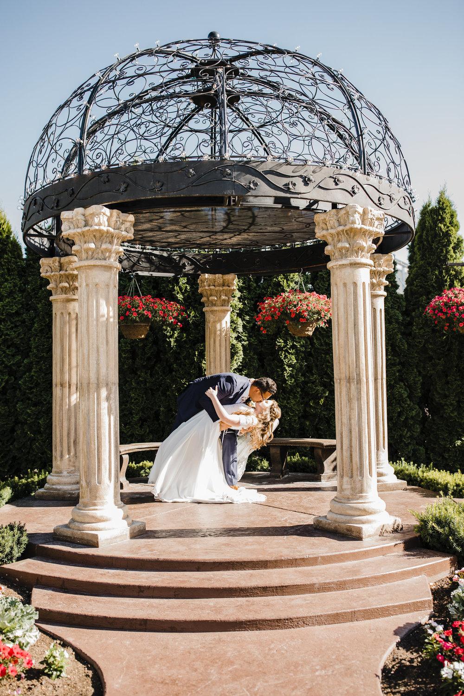 professional salt lake city photographer wedding arch gazebo kidding dip kissing