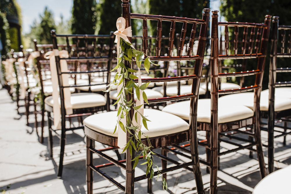 wedding day chair decorations greenery and pink ribbon on wooden chairs professional utah wedding photography